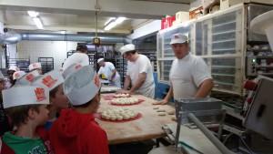 Bäckermeister Lob beschreibt die einzelnen Arbeitsschritte vom Teig zum Brötchen. Derweil hat eine Maschine aus dem großen Teig 30 Rosinenweckchen geformt.
